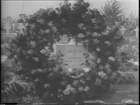 wreath in military cemetery at camp anfa / pan up flagpole to waving american flag / soldier marches in front of the anfa hotel / anfa hotel exterior... - allied forces stock videos & royalty-free footage