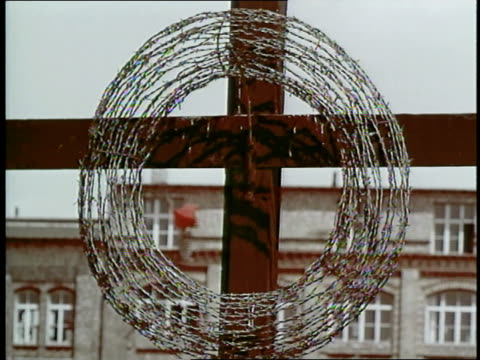a wreath of barbed wire hangs on a cross on the berlin wall germany - domination stock videos & royalty-free footage
