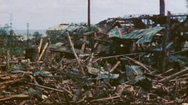 Wreckage in town and infantry and tanks advancing during World War II / Tinian Mariana Islands