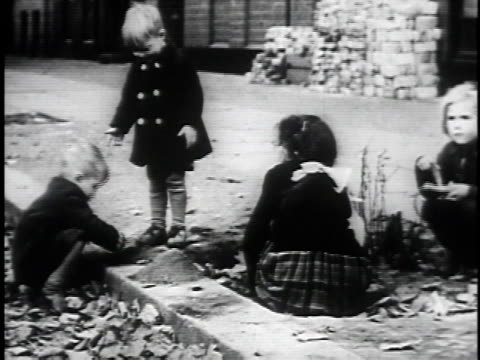 vídeos de stock, filmes e b-roll de wreckage of berlin / children playing in rubble / room of british women and german children at a table / ms two women and german child / spraying... - 1945
