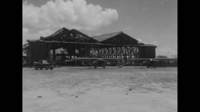 wreckage of japanese planes / two shots of captured japanese planes in front of hangar / vs captured japanese planes / us jeeps and trucks driving... - saipan stock videos and b-roll footage
