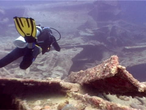 Wreckage of the British World War II cargo ship 'Thistlegorm', diver swimming over wreck, Red Sea