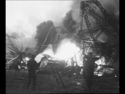 wreckage of the crashed hindenburg burns on ground as workers wander around the area / pan length of hindenburg with flames burning behind the... - ヒンデンブルク号点の映像素材/bロール
