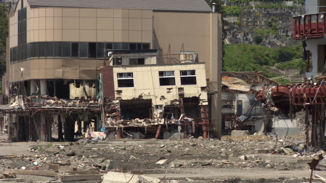 wreckage surrounds buildings still standing in the wake of an earthquake. - earthquake stock videos and b-roll footage