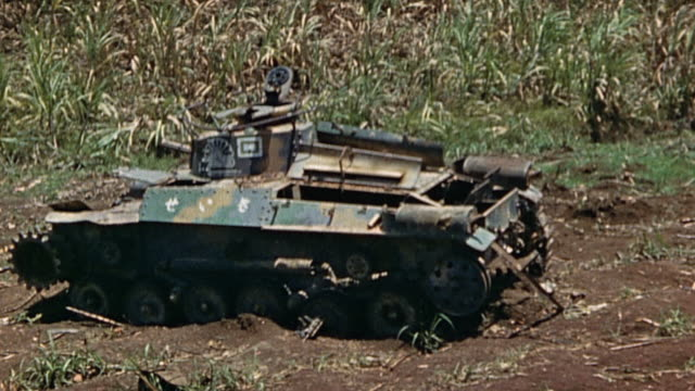 wrecked and partially dismantled japanese tank treads missing in a field at edge of jungle during wwii pacific campaign¬† - 装甲車点の映像素材/bロール