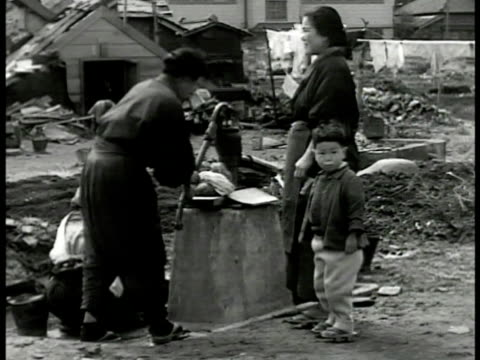 wrecked building japanese workers digging fg. japanese women pumping water child destroyed village bg. trolley passing on street bombed building bg.... - pacific war video stock e b–roll