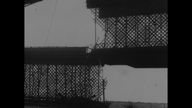 vídeos de stock e filmes b-roll de vs wrecked city street wrecked locomotive at destroyed bridge / seemingly cheerful poles rubble at end of an askew bridge latticework with gaping... - 1939