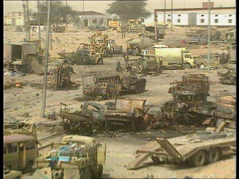 Wrecked Iraqi convoy IRAQ KuwaitBasra Road Road littered with destroyed abandoned Iraqi army vehicles pair of boots wrecked cars covered body TGV...