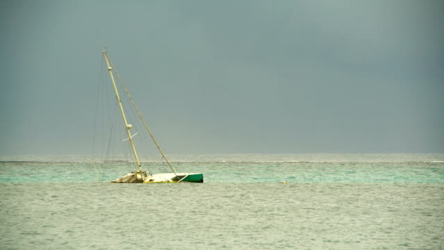 Wrecked sailing yacht after typhoon storm sinking Tahiti