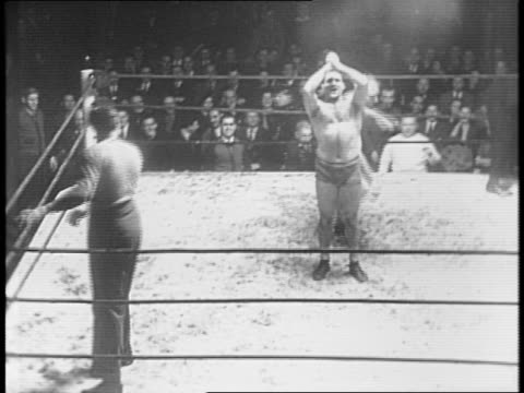Wrestlers Rufus Jones Michel Leone and Count Von Zuppe exchange blows as Max Baer referees / spectators look on / Michel Leone emerges victorious