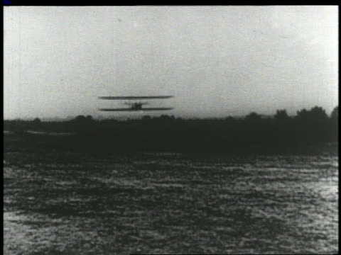 vídeos de stock e filmes b-roll de wright brothers' airplane flying low over camera on airfield - 1903