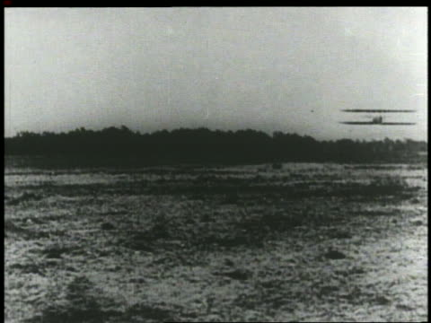 vídeos de stock e filmes b-roll de wright brothers' airplane flying low over ground on airfield - 1903