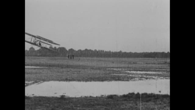 vídeos de stock, filmes e b-roll de wright brothers' biplane flying low over swampy ground possibly in le mans france in 1908 / airplane taking off from catapult with boom lowering... - orville wright