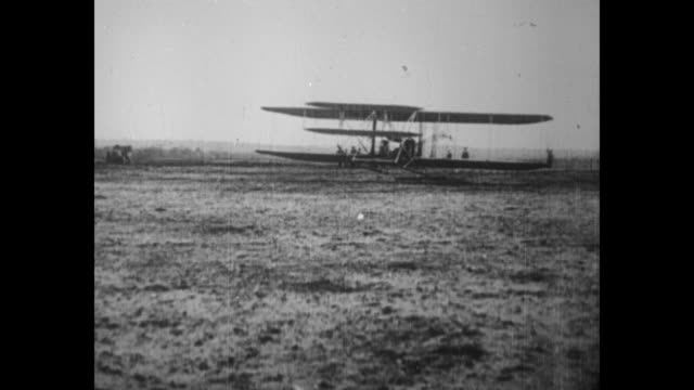 vídeos de stock, filmes e b-roll de vs wright brothers' plane takes off flies over muddy field possibly in le mans france in 1908 / note exact month/day not known - orville wright