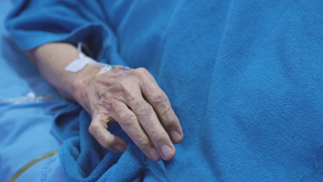 wrinkled elder hand with iv drip tube in hospital bed - bed stock videos & royalty-free footage
