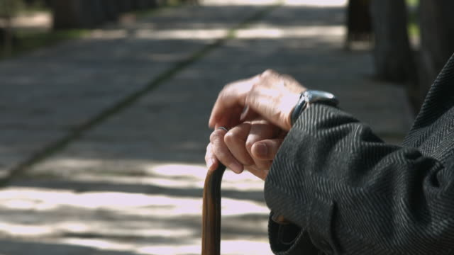 Wrinkled hands holding walking cane