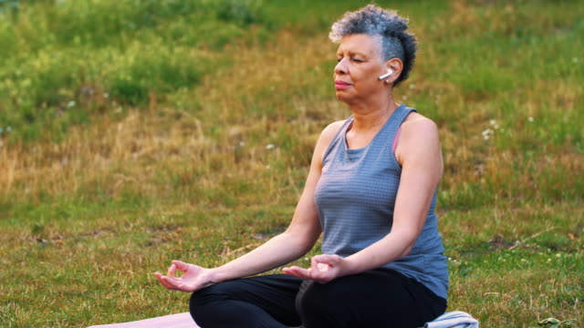wrinkled woman with in-ear headphones meditating on mat in park - grey hair stock videos & royalty-free footage