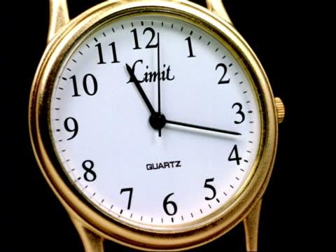 T/L Wrist watch - black hands turn on gold watch, white clock-face