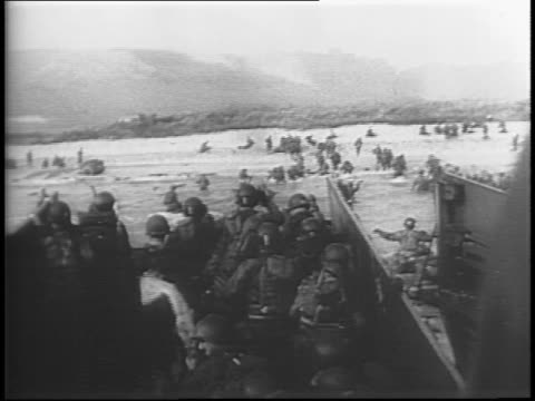 00 am / soldiers crowd into landing boats beginning dday invasion / shot from aboard boat soldiers on landing craft approaching beach / soldiers... - normandie stock-videos und b-roll-filmmaterial