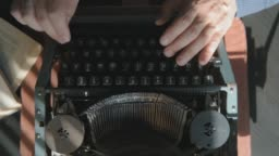 Writer typing with retro writing machine. Sun lights on the hand.
