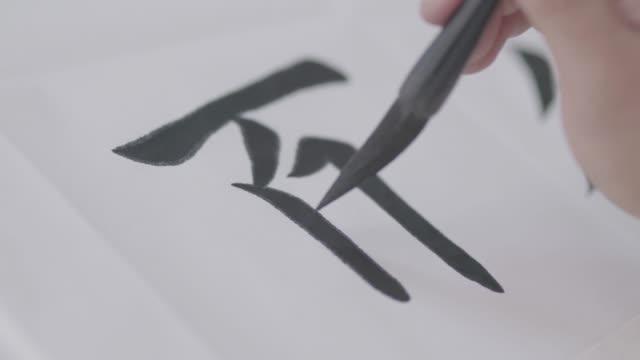 schreiben der chinesischen kalligraphie auf reispapier, log-farbmodus - kalligraphieren stock-videos und b-roll-filmmaterial