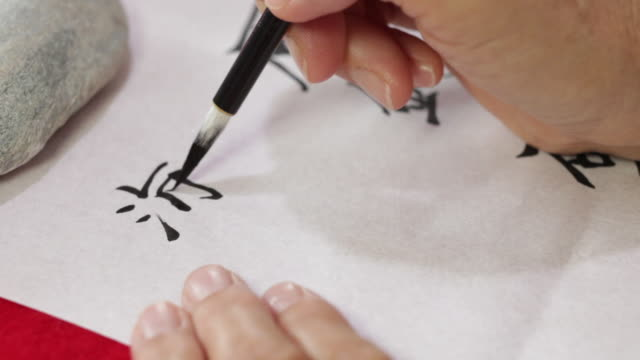 writing japanese calligraphy with a brush - kalligraphieren stock-videos und b-roll-filmmaterial