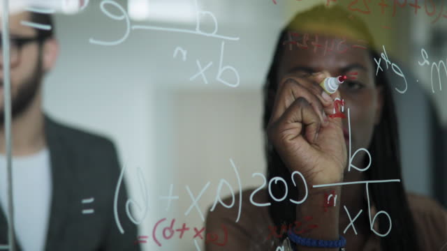writing mathematical formulas on glass board - scientist stock videos and b-roll footage