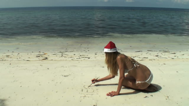 writing merry christmas on wild beach; woman with santa's hat - santa hat stock videos & royalty-free footage
