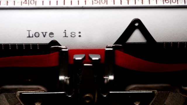 writing short phrase 'love is' with an old typewriter - short phrase stock videos and b-roll footage