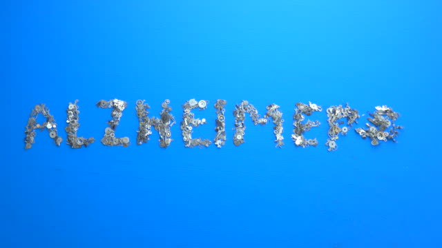 Writing Word ALZHEIMER'S With Metal Clockworks On blue background
