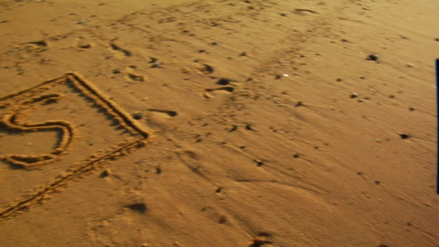 """cu, pan,  """"sos"""" written in sand, provincetown, massachusetts, usa - sos stock videos and b-roll footage"""