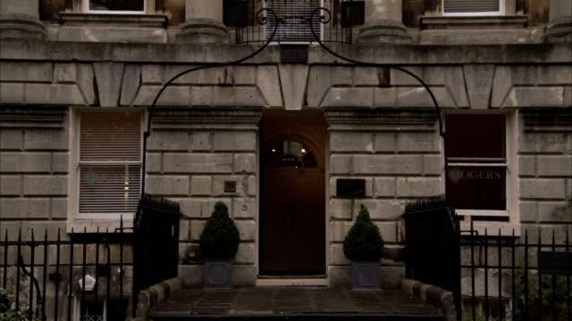 vídeos y material grabado en eventos de stock de a wrought iron arch frames the front door of a townhouse. available in hd. - frontón característica arquitectónica