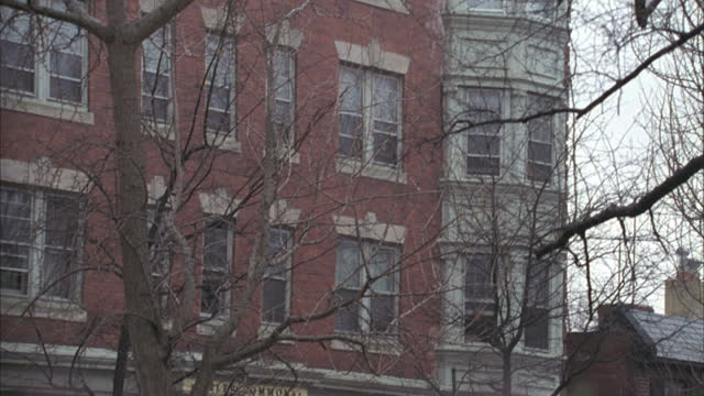 a wrought iron fence surrounds an apartment building in philadelphia. - bay window stock videos & royalty-free footage