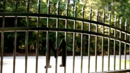 Wrought iron gate opening to the left. Home driveway.