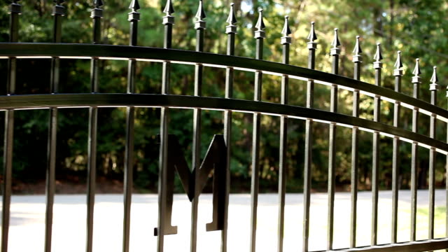 wrought iron gate opening to the left. home driveway. - fence stock videos & royalty-free footage