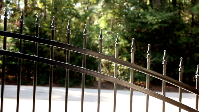wrought iron gate opening to the left. home driveway. - automatic stock videos & royalty-free footage