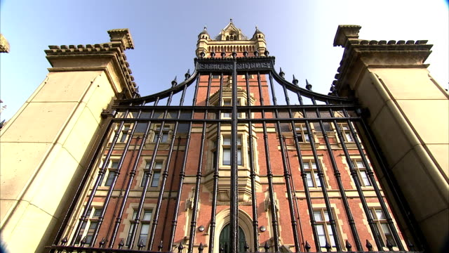 A wrought iron gate stands at an entrance to the University of Manchester. Available in HD.