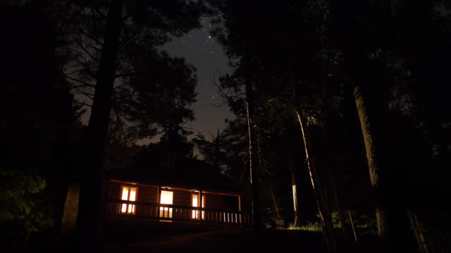 ws t/l stars and clouds above cabin in the woods / quebec city, quebec, canada - capanna di legno video stock e b–roll