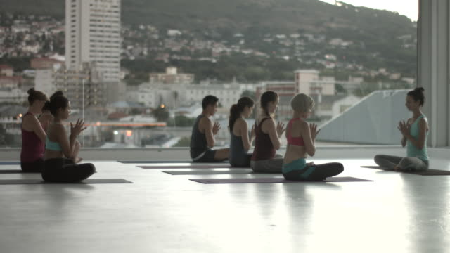 vídeos de stock, filmes e b-roll de ws_big yoga class meditating, in rooftop studio - posição de lótus