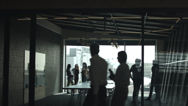 ws_businesspeople standing up and talking in groups, before ceo walking in and presenting new female creative director - salutarsi video stock e b–roll