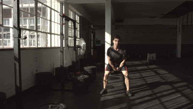 vídeos de stock e filmes b-roll de ws_cross training guy using kettlebell in gym gym - aperfeiçoamento pessoal