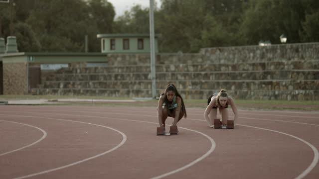 WS_Female athletes adjusting start blocks on the track