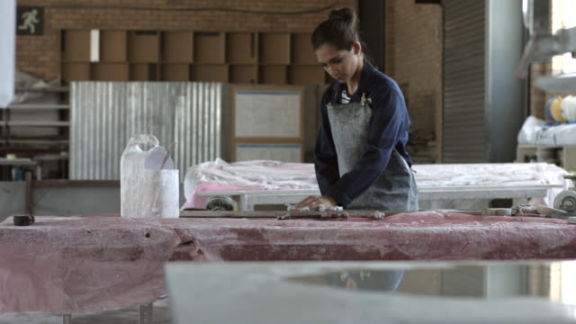 ws_female factory worker wiping marble slab - genderblend video stock e b–roll