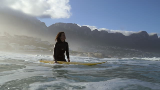 ws_female surfer in the ocean with surfboard - anticipation stock-videos und b-roll-filmmaterial