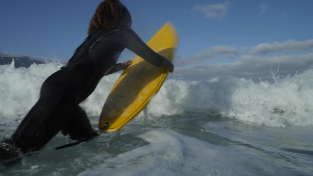 WS_Female surfer jumping in the ocean with surfboard