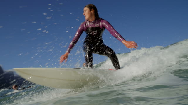 vídeos de stock, filmes e b-roll de ws_female surfer riding wave - surfe