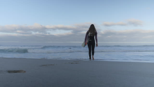 ws_female surfer walking into the sea with board - lockdown viewpoint stock videos & royalty-free footage