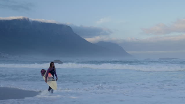 WS_Female surfer walking on the beach with board