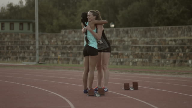 ws_female track athletes hugging on the track - track and field event stock videos & royalty-free footage