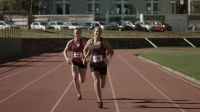 WS_Female track athletes running on track